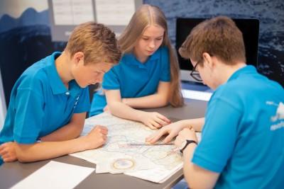 Andreas Aasen (16), Lars Rønhaug Pettersen (16) og Caroline Sofie Pedersen (16) planlegger sin flytur. Bilde: Marte Antonsen.